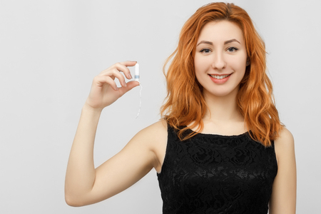 Beautiful young smiling girl with long hair holding a female swab isolated on white background. In his hand of a menstrual tampon isolated on a white background. Menstruation time. Hygiene
