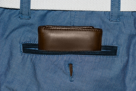 Brown leather purse in the pocket. Wallet halfway out from a jeans back. Pocket blue jeans with Wallet brown color Stock Photo
