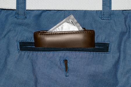 cb336b66a Billetera en un bolsillo de jeans azul con condón de plata. Foto de archivo  -