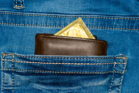 wallet in a pocket of blue jeans with a gold condom.