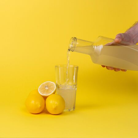 Lemon juice is poured into a glass with a glass bottle. Whole and cut lemons lie nearby.
