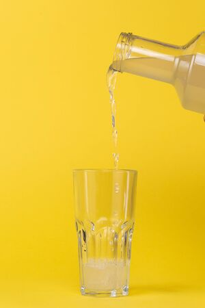Lemon juice is poured into a glass with a glass bottle. Stok Fotoğraf