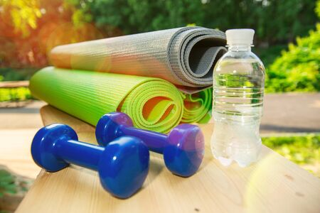 three roll-up sports mats with blue dumbbells and water on a wooden floor in a park outside with the setting summer sun. Healthy lifestyle concept. Banco de Imagens