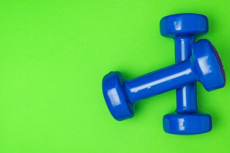 Two blue of dumbbells Isolated on green background.
