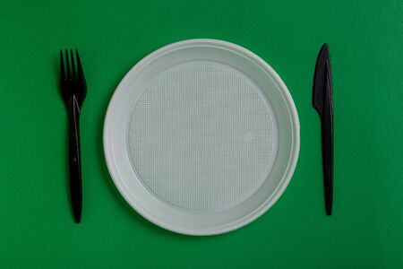 Plastic disposable utensils on green background. fork, knives, plates