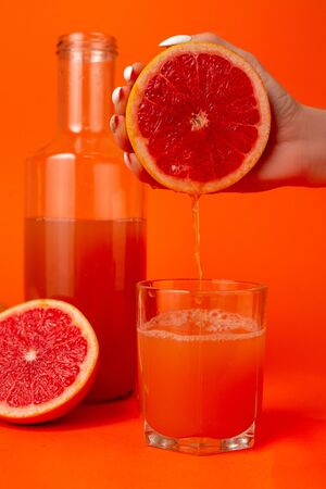 Close up cropped photo of female holding in hands half of fresh ripe grapefruit, glass cup isolated on orange wall background. People vivid lifestyle relax vacation concept. Mock up copy space