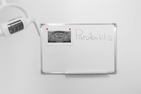 Dental office. Whiteboard with an inscription in Latin parodontitis and a photo of an x-ray of teeth on it(magnetic board) isolated on white