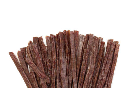 Dried beef meat sliced on stick, beer snack isolated on white background