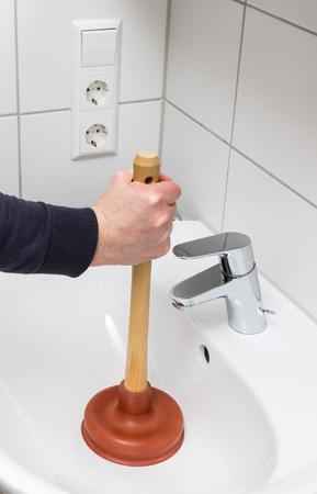 A Plumber Using Plunger In Bathroom Sink