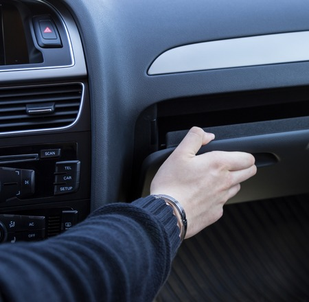 mans hand taking on glove compartment of cars
