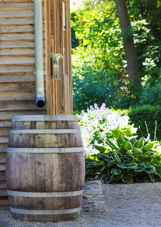 Wooden Rain Barrel collecting runoff from roof through gutters. Stock Photo
