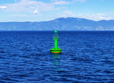 A green channel marker buoy
