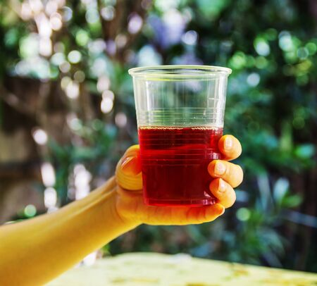 Glass with raspberry juice in hand Stock Photo