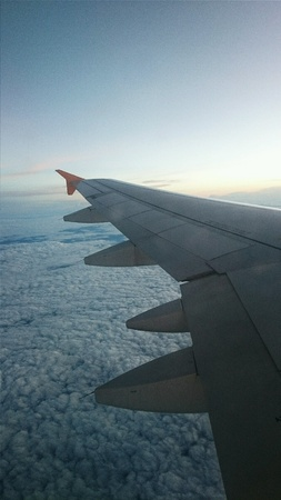 wingspan: View of wings on the clouds from airplane windows Stock Photo