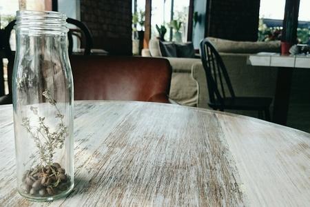 flores secas: Los granos de caf� y flores secas en una botella de vidrio de mesa de madera en el caf Foto de archivo