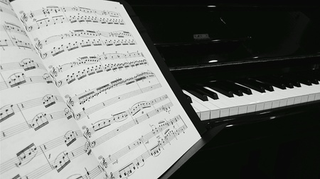 background: Piano sheet music with piano at the background Stock Photo