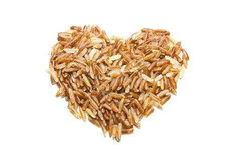 heart shape brown rice isolated on white background Stock Photo
