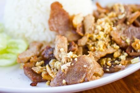 Gebratenes Schweinefleisch mit Knoblauch und Pfeffer an Reis