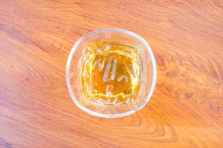 Ein Glas Eistee auf Holz.