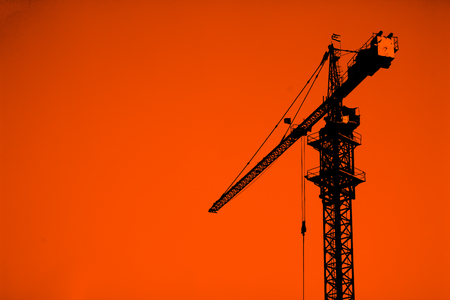 cranes on a construction site behind buildings photo