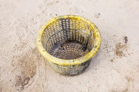 cesto basura: amarillo cesta de la basura en la arena Foto de archivo