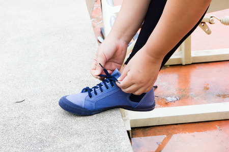 lacing sneakers: woman tying laces of running shoes Stock Photo