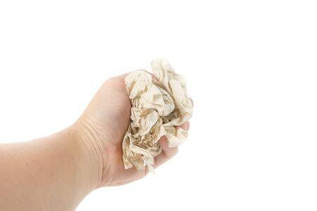ball lump: hand holding Crumpled brown napkin on white background