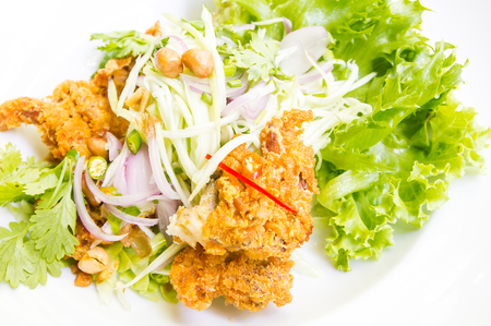 Deep fried soft shell crab with spicy salad on white plate