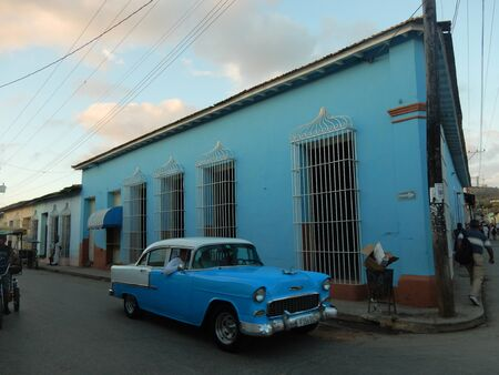 bilding: A blue 1950s American car with a blue bilding at dusk, Trinidad, Cuba