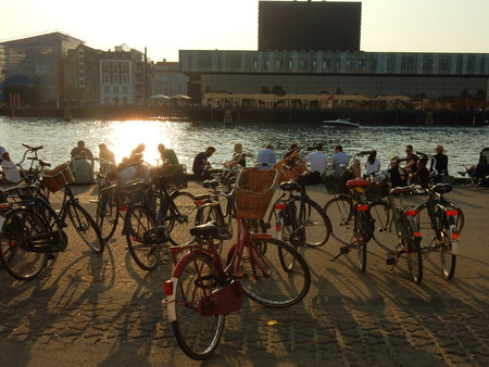 playhouse: bicycles and people on a wharf in front of royal danish playhouse, Copenhagen harbor, Denmark