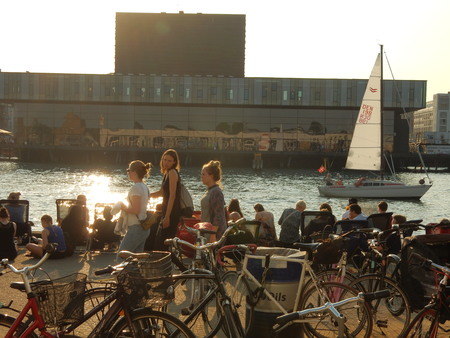 playhouse: bicycles and people on a wharf in front of a sailing boat and royal danish playhouse, Copenhagen harbor, Denmark Editorial