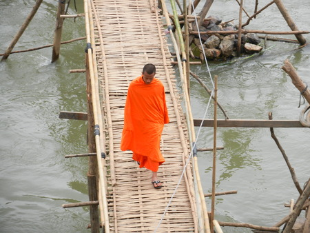 nam: a buddhist monk walking on the bamboo bridge over the Nam Khan River, Luang Prabang, Laos