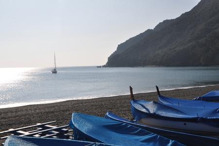 a sailing boat moored off Riva Trigoso beach in winter with ashore fishing boats, Genoa Province, Liguria, Italy