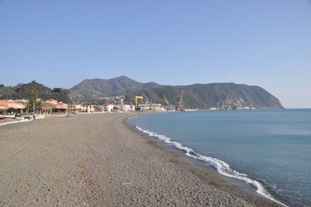 the empty beach in Riva Trigoso in winter with a sailing boat in the sun rises, Liguria, Genoa Province, Italy