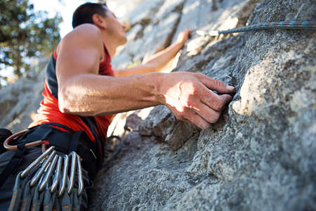 Climber in red t-shirt climbs a gray rock. A strong hand grabbed the lead, selective focus. Strength and endurance, climbing equipment: rope, harness, chalk, chalk bag, carabiners, braces, quickdraws