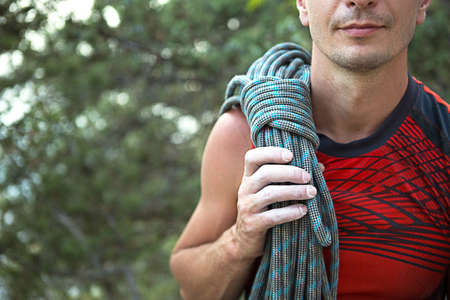 A male climber of Caucasian appearance with a coiled rope on his shoulder. Hand in white magnesia. Red sports Jersey, extreme sports, rock climbing. Space for text
