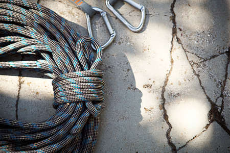 Coiled climbing rope and steel carabiner. Mountain climbing equipment: harness, brakes, quickdraws, self-insurance, belay device eight. On a stone background with cracks. Flatlay, copy space