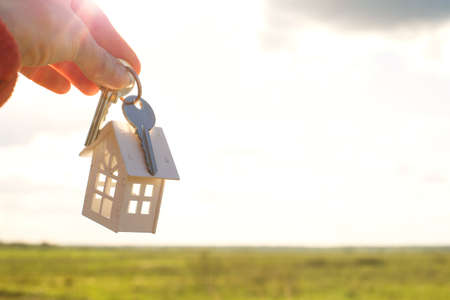 White wooden figure of a house and keys in hand against the background of the sky and field. Dream of your home, building a cottage in the countryside, plan and design, delivery of the project, moving to a new house. Stock Photo