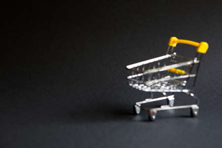 Empty grocery cart in the defocus from a supermarket on a black background. Black Friday, shopping cart, shopping, online store, sale, discounts. Space for text. Blurred