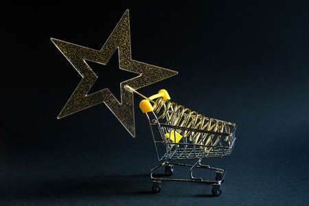 Shopping cart with a gold transparent star with sequins in the shape of a Christmas tree on a black background. Black Friday, buying gifts for the new year. Space for text