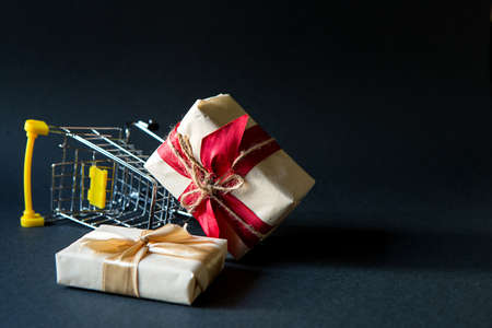 Box with a gift in Christmas packaging in a shopping cart on a black background. Black Friday, buying gifts for the new year. Space for text