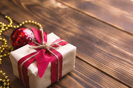 A box with a Christmas gift in light paper is tied with a red ribbon on a wooden background with decor. Christmas tree pendant, beads, garland. New Year. space for text