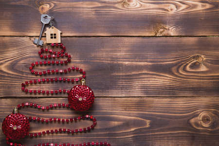 Key to the house with a keychain on top of Christmas tree made of red square beads. Flat lay on wooden background. Building or buying a house in new year. Mortgage, real estate rental. Space for text Stock Photo