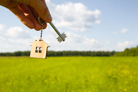 Wooden pendant of a house and key. Background of the sky and field. Dream of home, building a cottage in the countryside, plan and design, delivery of the project, moving to a new house. Copy space