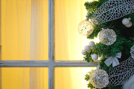 Christmas decorations made of spruce branches and white transparent balls and ribbons frame the window with wooden frame and yellow light. New year festive atmosphere, comfort of home. Space for text