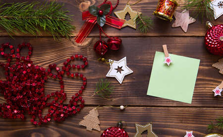 Christmas flat lay of red balloons and wooden stars and clothespins on a dark background with a square sheet for notes in the center. New year's frame, space for text. Xmas toys, beads, pine branches