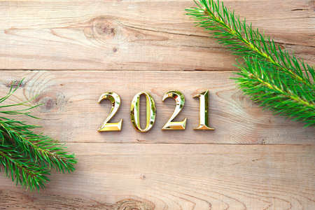 Gold numbers 2021 on a wooden background with Christmas decorations: green branches of spruce, red ball. New Year concept, frame, top view. Copy space. Merry Christmas and Happy New Year symbol's