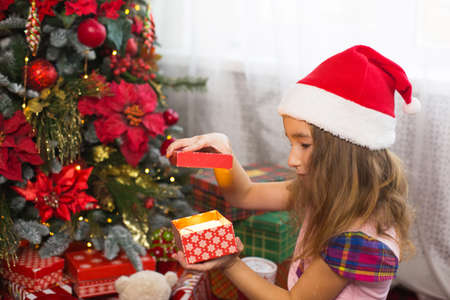 Little girl in Santa hat opens a red box with a gift and a Golden magic light near the Christmas tree. Holiday decor, poinsettias on fir trees, New year. Joy, surprise, children's emotions. Copyspace Stock Photo