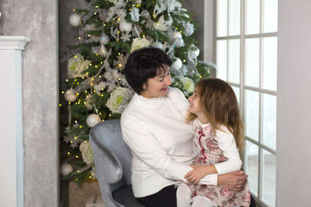 Grandmother with a little girl on the background of Christmas decorations and a large window. Family holiday, emotions, gift box. Granddaughter on granny's lap. New Year