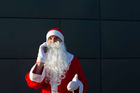 Modern Santa Claus talking on the phone. Ordering the services of an animator for the Christmas and new year. Online greetings via the Internet and mobile communication, social distance